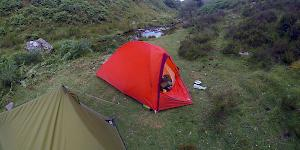 Image showing the bright Orange Vaude Hogan UL Argon pitched next to the modest green MSR tent.
