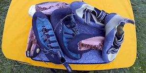 The picture shows a pile of climbing shoes of varying ages spread out on a bouldering pad.