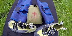 Picture of two knee support bandages with a pair of aggressive climbing shoes and a personal first aid kit spread out on a bouldering pad.