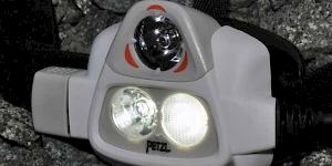 Close up image of the Petzl Nao 575L showing the light sensor at the top and the two lamps below. to the left of the picture the control dial can be seen.