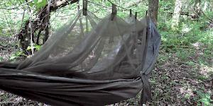 Image of the Snugpak Jungle Hammock pitched in woodland with the integrated mosquito net suspended above and a sleeping bag inside..
