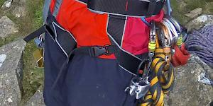 Side-on image showing the DMM Super Couloir being worn, clearly showing the quick release leg buckles, double back buckle waist closure and the simple waist attachment through the belay loop.