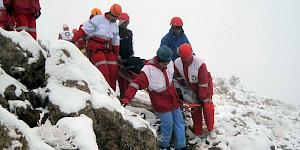 Mountain Rescue team evacuating a stretcher casualty off the mountain in snowy terrain.